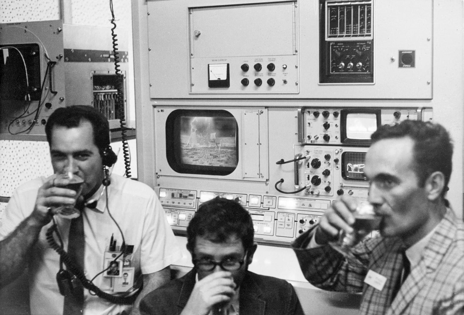 Three men seated drinking from glasses, seated in front of electronic equipment